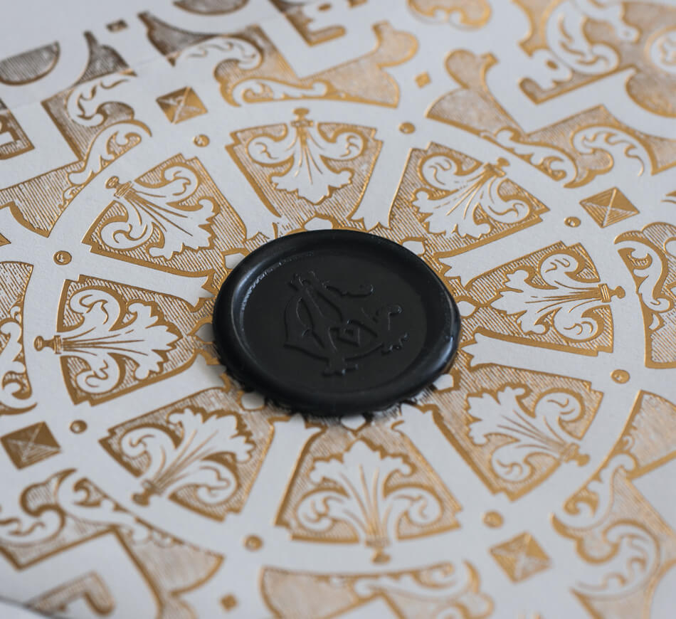 Black wax seal on gold and ivory envelope