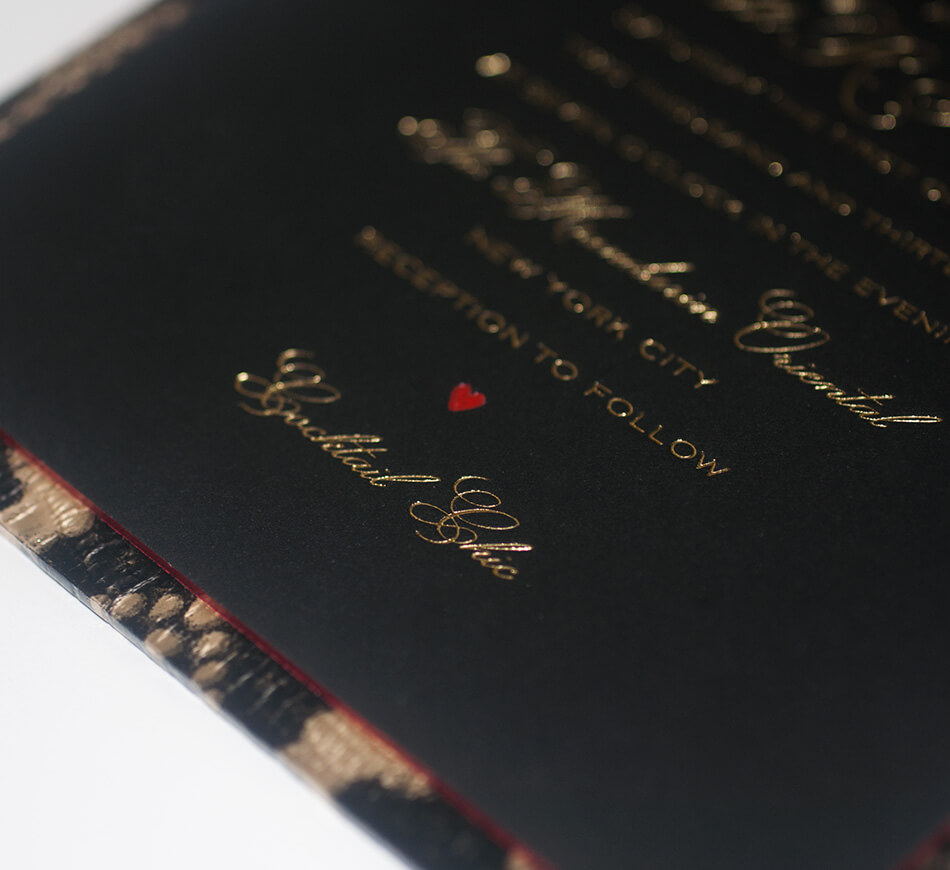 Gold calligraphy lettering on a black invite