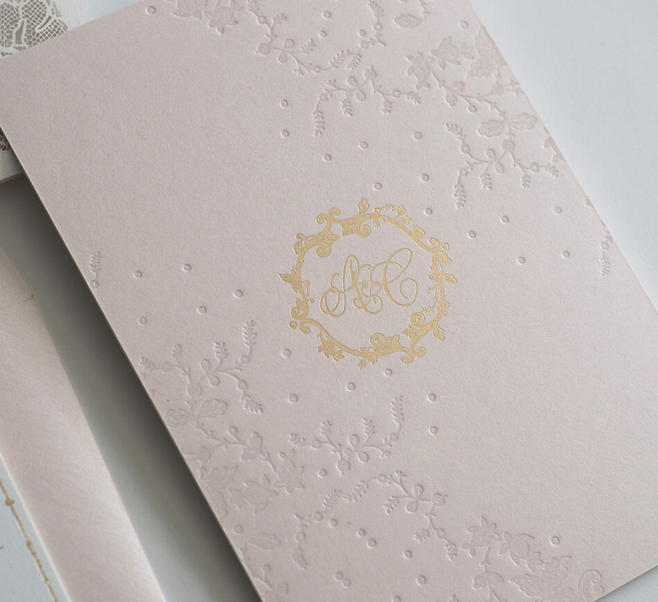 Gold monogram on blush invitation backer