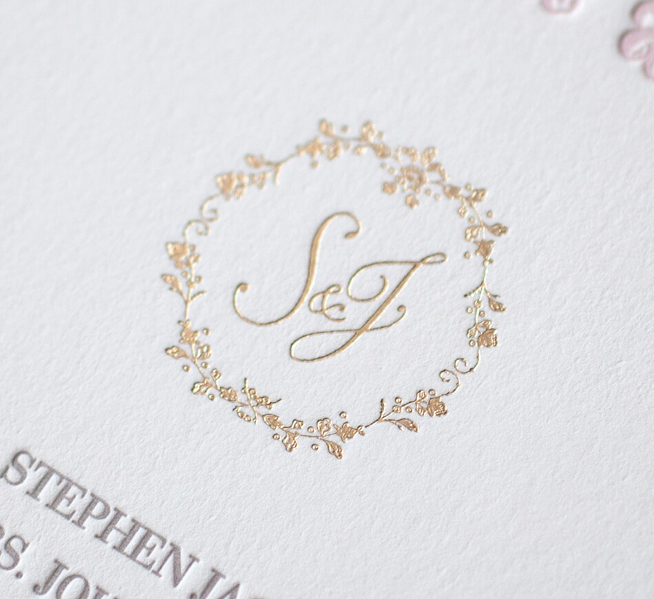 Gold script monogram with a floral border