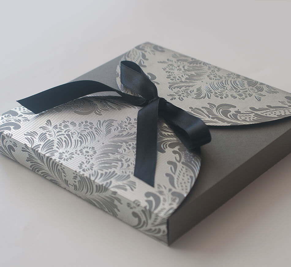 Silver foil stamped box with a ribbon