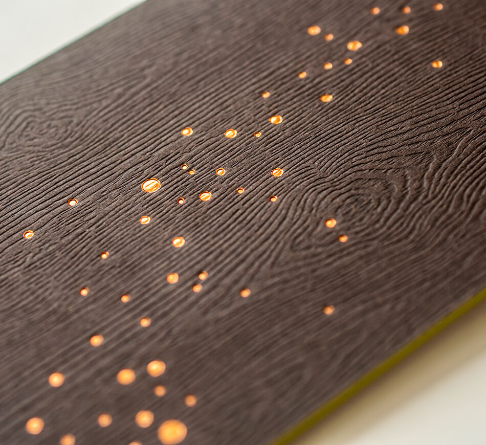 Copper foil fireflies on wood embossed paper