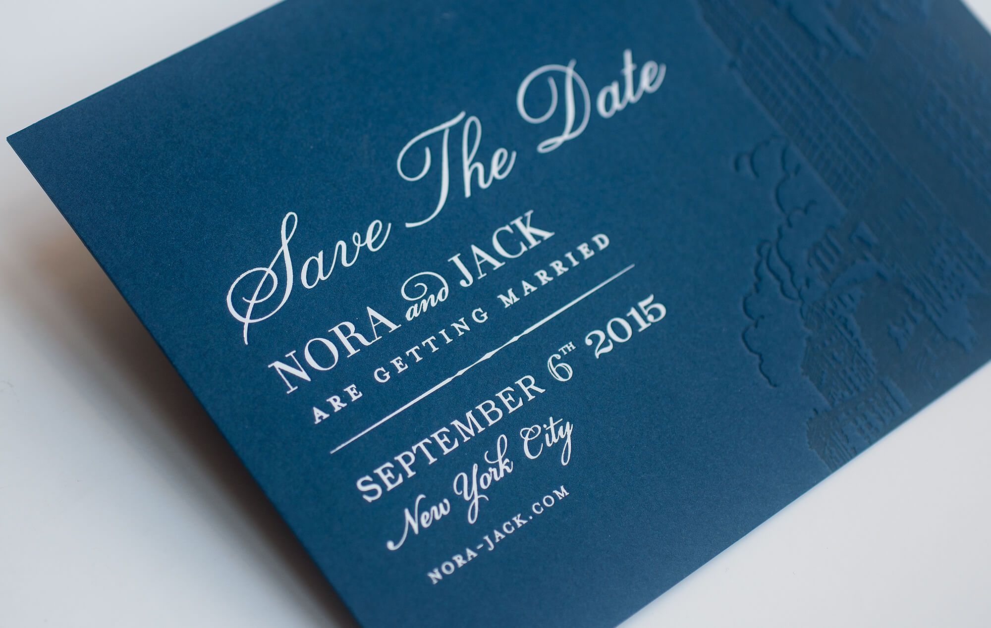 White foil on a navy blue save the date