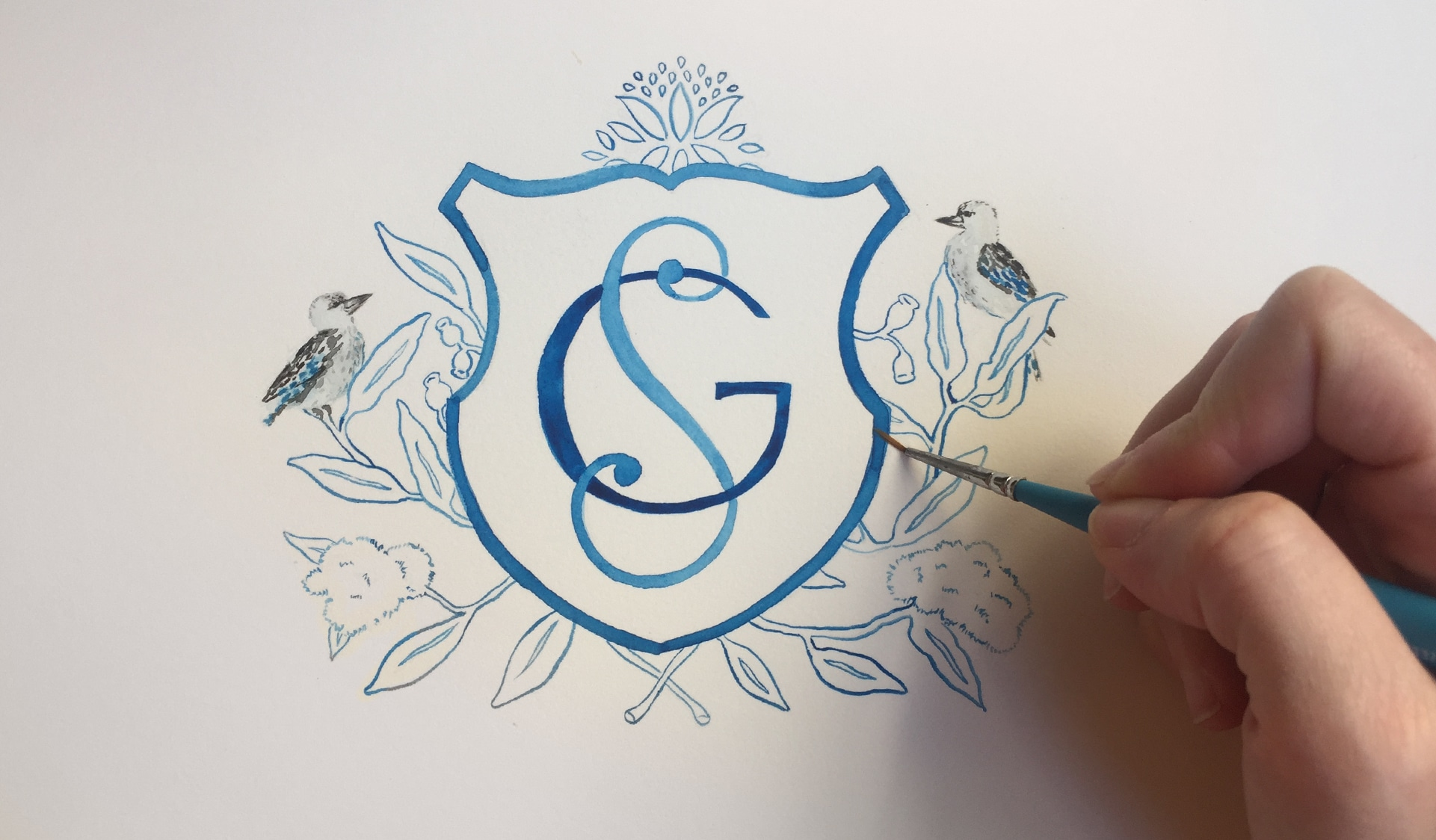 Watercolor painting of crest and monogram